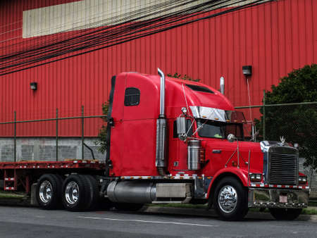 a red truck in front of a red hall