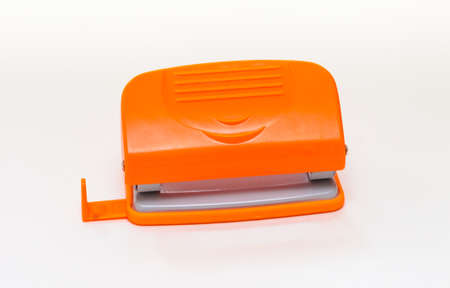 Orange and gray hole punch on a white background Stock Photo