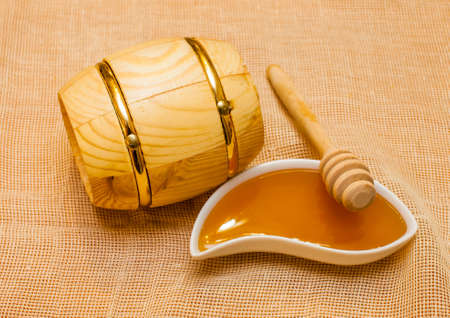 Wooden barrel and a bowl of honey on a beige napkin