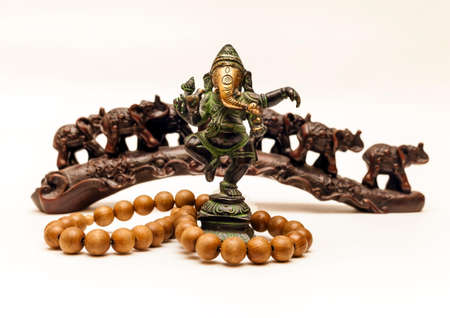 Indian Souvenirs: Bronze Ganesha, wooden beads and plastic elephants in the background on a white background Stock Photo