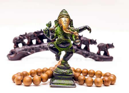 Recuerdos indios: Bronce Ganesha, cuentas de madera y elefantes de plástico en el fondo sobre un fondo blanco