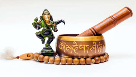 Indian Souvenirs: Bronze Ganesha, wooden beads and bronze singing bowl on white background