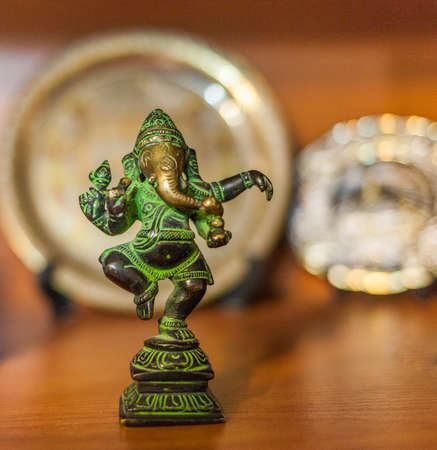 bronze figurine of Ganesha on a colored background