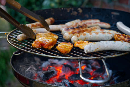 Grilled food on the barbecue with glowing charcoal