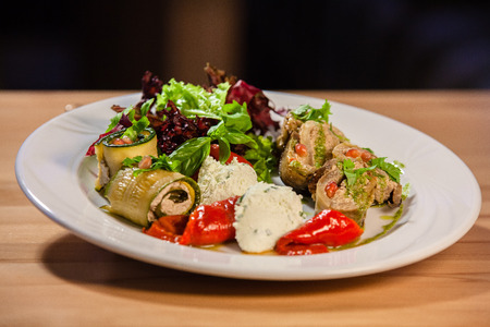 Delicious meat rolls and rolls of zucchini stuffed with nuts and cheese filling, cheese gnocchi, roasted pepper and salad on a white plate