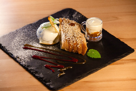 Piece of apple strudel with vanilla ice cream ball, cup of cream decorated with caramel and chocolate sauces, mint leaves, icing sugar and sesame on a black board on wood background Stock Photo