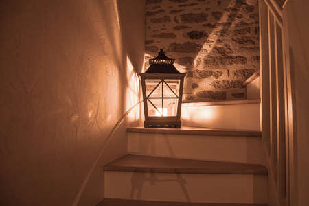 a large lantern with a burning candle on a wooden staircase and shadows and light aspects falling in all directions, in the background is a stone wall Zdjęcie Seryjne