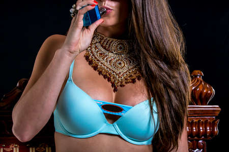 Sexy Model with blue bra and boy shorts smoking with necklace