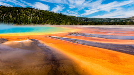 The Grand Prismatic Spring in Yellowstone National Park is the largest hot spring in the United States. It is located in the Midway Geyser Basin.Striking colors like the rainbow dispersion of white light by an optical prism: red, orange, yellow, green, an 版權商用圖片 - 79608891