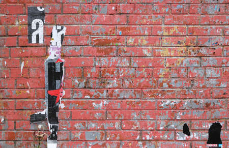 Red bricks urban street wall with remnants of pasted posters backdrop.