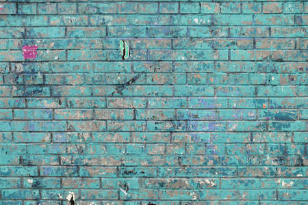 Blue brick with remnants of pasted posters. Wall texture