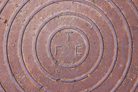 Rust metal hatchway with circlec ornament. Urban city street art. Stock Photo
