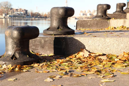 Ship Bollards on Granite Steps with Autumn Leaves. Saint-Petersburg. Stock Photo
