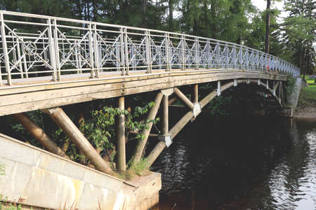 Concrete wood bridge with decorative ornaments on handrail. Park forest trees with small river.
