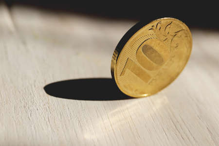 10 rubles copper coin on white wood texture. Stock Photo