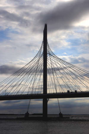 Massive cable-stayed bridge side construction. Clouds in the sky. Stock Photo