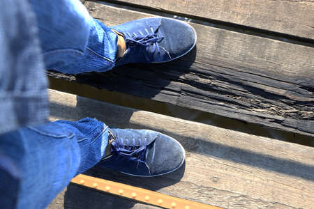 The feet of a man stand on an unstable wooden bridge.