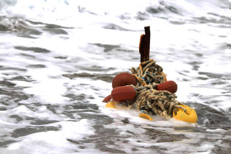 Iron stake with wound ropes and buoys in the breaking wave