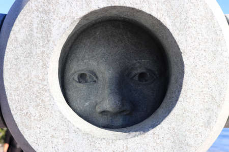 Carved out of blue granite woman holding a large ring. Female face looks and a large ring. 新聞圖片