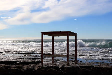 Table on a cliff with sea waves on background.
