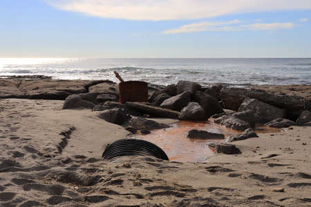 Drain tube with rusty barrel with log and big cobblestones on shoreline seascape.