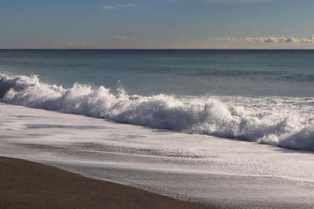 Calm sea with splashing wave and long foam on the beach seascape. Stock Photo