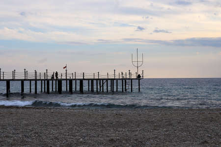 Fisherman on the pier. View from the beach.