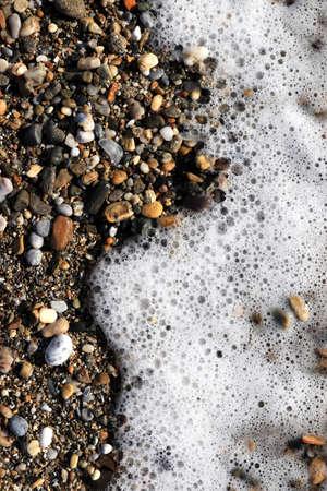 Sea stones on shore with sea wave foam background. Stock Photo