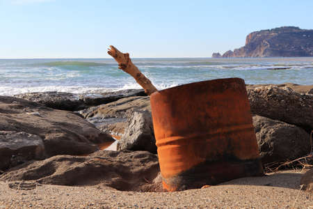 Barrel with log on the rocky beach with Bedesten Alanya fortress on background.
