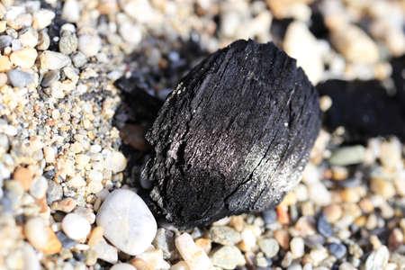 Coal on the beach stones. Stock Photo