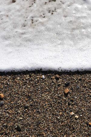 Sea wave foam on the beach sand. Marine summer background.