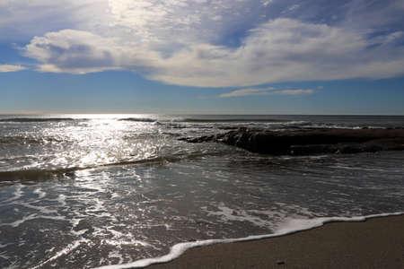 Rock shoreline in the sea with sunlight seascape.