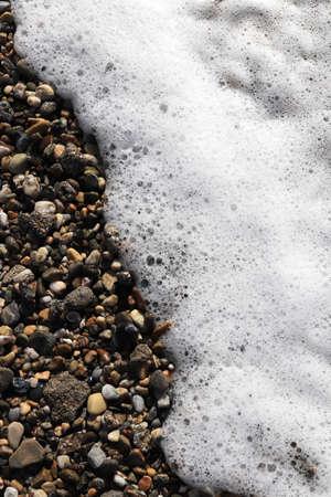 Sea water foam on the beach stones. Nautical marine summer background. Alanya. Turkey.