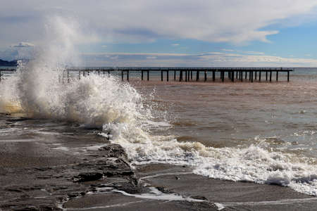 Pier seascape with splashing wave on foreground.