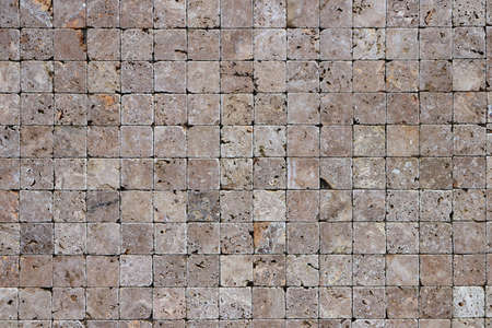 Square stones surface background. Travertine masonry tiles cladding wall texture. Banco de Imagens