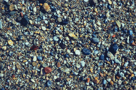 Lot of wet small stones on the beach with little pebbles texture. Nautical marine background. Reklamní fotografie