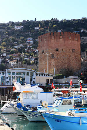Bedesten Alanya fortress main tower marina landscape. Moored boats in the bay. Turkey.