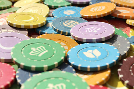 Many colored chips backdrop. Lot multicolor assorted gambling playing chips surface. Colorful casino chips background. Stock Photo