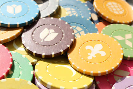 Many colored chips backdrop. Lot multicolor assorted gambling playing chips surface. Colorful casino chips background.