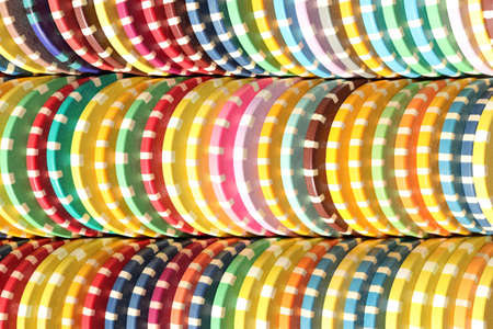 Many colored chips backdrop. Lot multicolor assorted gambling playing chips surface. Colorful casino chips stacks background.