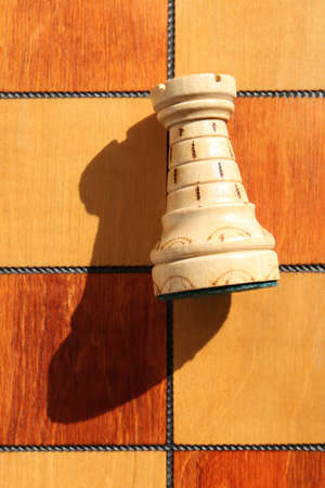 The figure of a white rook lies on a chess board. Wood game chess board background.