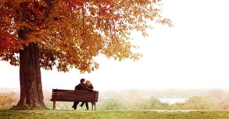 parejas enamoradas: Vew trasera de una pareja joven que se sienta y besarse en un banco en el hermoso día de otoño. El hombre está abrazando a su esposa hombro. Tiro horizontal.