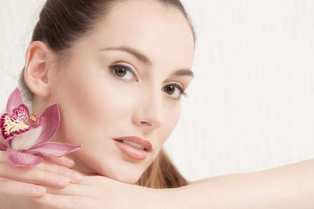 body conscious: Portrait of Beautiful Young Woman with Pink Orchid looking at Camera.