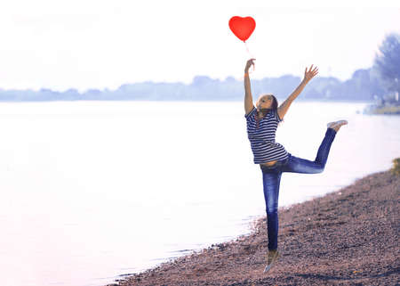 playful behaviour: Happy Young Woman Jumping on the Shore with a Red Shaped Heart Balloon