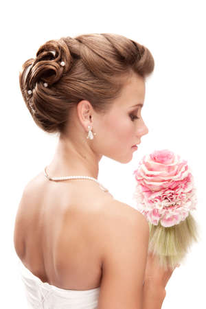 back shots: Beautiful bride with bouquet looking down at the white background