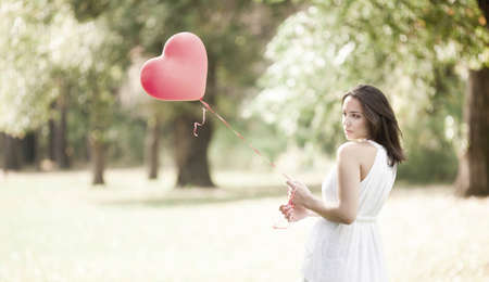 sad heart: Sad Young Woman Standing with a Red Shaped Heart Balloon Outdoors Stock Photo