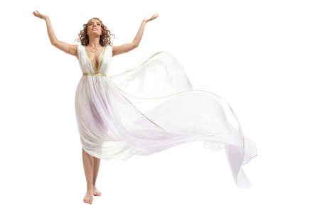 De mooie jonge vrouw dragen van witte en gouden Griekse Kostuum, opvoeding van haar armen op de witte achtergrond