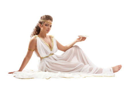 goddess: The Beautiful Young Woman Sitting on the Floor, Holding the Gold Bowl with Nectar and Wearing White and Gold Greek Costume on the White Background Stock Photo