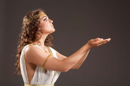 toga: La hermosa joven vestido de blanco y oro Traje griego, sosteniendo algo en sus manos en el fondo oscuro