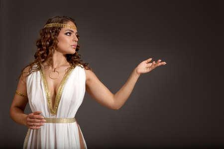 美しい若い女性の身に着けている白と暗い背景に彼女の左の何かを探して金のギリシャ語の衣装 写真素材